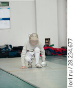 Купить «Fencer in white costume with rapier and protective mask stands up», фото № 28234677, снято 26 марта 2018 г. (c) Константин Шишкин / Фотобанк Лори