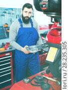 Купить «Smiling man worker fixing failed motorcycle», фото № 28235305, снято 24 сентября 2018 г. (c) Яков Филимонов / Фотобанк Лори