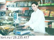 Купить «Smiling female seller weighing festive chocolate cake», фото № 28235417, снято 24 января 2017 г. (c) Яков Филимонов / Фотобанк Лори