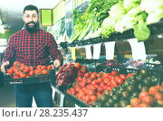 Купить «Assistant demonstrating tomatoes», фото № 28235437, снято 15 ноября 2016 г. (c) Яков Филимонов / Фотобанк Лори