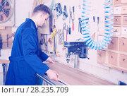 Купить «Man laying board to drill», фото № 28235709, снято 7 ноября 2016 г. (c) Яков Филимонов / Фотобанк Лори