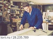 Купить «guy using chisel to process plank at workshop», фото № 28235789, снято 7 ноября 2016 г. (c) Яков Филимонов / Фотобанк Лори