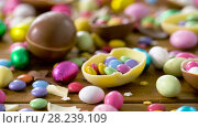 Купить «chocolate easter eggs and drop candies on table», видеоролик № 28239109, снято 24 марта 2018 г. (c) Syda Productions / Фотобанк Лори