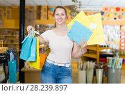 Купить «Smiling woman buys packages for gifts», фото № 28239897, снято 19 апреля 2017 г. (c) Яков Филимонов / Фотобанк Лори