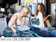 Купить «Two glad girls choosing denim trousers», фото № 28239989, снято 4 апреля 2020 г. (c) Яков Филимонов / Фотобанк Лори