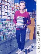 Купить «Young man bearing pile of discs during shopping», фото № 28240281, снято 15 февраля 2018 г. (c) Яков Филимонов / Фотобанк Лори