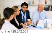 Купить «Employees are writing financial reports and discussing with mature boss in the office.», видеоролик № 28242561, снято 2 июля 2017 г. (c) Яков Филимонов / Фотобанк Лори