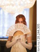 Купить «Attractive red haired woman in vintage 18 centuries dresses use fan in luxury ballroom», фото № 28244305, снято 30 марта 2018 г. (c) Константин Шишкин / Фотобанк Лори