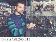 Купить «Male looking baitcasting reel for rod in the sports shop», фото № 28245313, снято 16 января 2018 г. (c) Яков Филимонов / Фотобанк Лори
