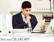 Купить «Adult office worker is reading documents about the transaction», фото № 28245497, снято 18 мая 2017 г. (c) Яков Филимонов / Фотобанк Лори