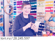 Купить «Smiling mature woman with smartphone after shopping», фото № 28245597, снято 10 мая 2017 г. (c) Яков Филимонов / Фотобанк Лори