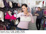 Купить «Woman selecting bra in lingerie store», фото № 28245705, снято 24 октября 2018 г. (c) Яков Филимонов / Фотобанк Лори