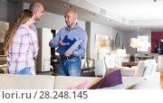 Купить «Sales assisstant is showing prices in home furnishings store», фото № 28248145, снято 16 мая 2017 г. (c) Яков Филимонов / Фотобанк Лори