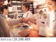 Купить «Nail technicians performing manicure», фото № 28248489, снято 28 апреля 2017 г. (c) Яков Филимонов / Фотобанк Лори