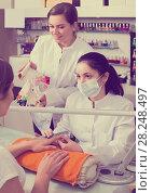 Купить «smiling nail technician offering to female client to choose color of nail polish in beauty salon», фото № 28248497, снято 28 апреля 2017 г. (c) Яков Филимонов / Фотобанк Лори