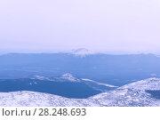 Купить «Winter wooded mountains with a snow peak or a volcano cone in the distance», фото № 28248693, снято 24 марта 2018 г. (c) Евгений Харитонов / Фотобанк Лори