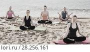 Купить «Sporty females meditating in yoga position Padmasana on seaside», фото № 28256161, снято 22 мая 2017 г. (c) Яков Филимонов / Фотобанк Лори