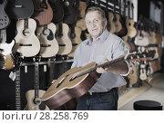 Купить «male demonstrates an acoustic guitar», фото № 28258769, снято 18 сентября 2017 г. (c) Яков Филимонов / Фотобанк Лори