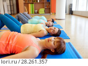 pregnant women lying on mats in gym. Стоковое фото, фотограф Syda Productions / Фотобанк Лори