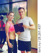 Купить «smiling young woman with personal trainer in gym», фото № 28261437, снято 29 июня 2014 г. (c) Syda Productions / Фотобанк Лори