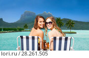 Купить «happy young women with drinks sunbathing on beach», фото № 28261505, снято 11 июля 2013 г. (c) Syda Productions / Фотобанк Лори