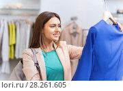 Купить «happy young woman choosing clothes in mall», фото № 28261605, снято 19 февраля 2016 г. (c) Syda Productions / Фотобанк Лори