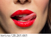 Купить «close up of woman with red lipstick licking lips», фото № 28261661, снято 5 января 2018 г. (c) Syda Productions / Фотобанк Лори