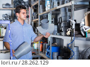 Купить «attentive male is choosing plastic trumpet in the plumbing department in store», фото № 28262129, снято 26 июля 2017 г. (c) Яков Филимонов / Фотобанк Лори