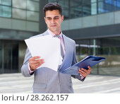 Купить «Satisfied businessman holding agreement papers», фото № 28262157, снято 8 мая 2017 г. (c) Яков Филимонов / Фотобанк Лори