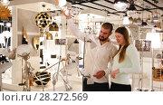Купить «Smiling couple customers choosing lamp in furniture shop», видеоролик № 28272569, снято 13 февраля 2018 г. (c) Яков Филимонов / Фотобанк Лори