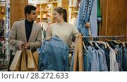 Купить «Couple is choosing jeans shirt for her in the clothes store.», видеоролик № 28272633, снято 27 марта 2018 г. (c) Яков Филимонов / Фотобанк Лори
