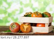 Купить «Wooden box with persimmon, near on burlap whole fruit and knife on table», фото № 28277897, снято 20 декабря 2017 г. (c) Сергей Молодиков / Фотобанк Лори