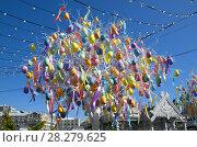 Купить «Москва. Благотворительный фестиваль «Пасхальный дар» на Площади Революции. Декоративное дерево с разноцветными яйцами на фоне голубого неба», фото № 28279625, снято 9 апреля 2018 г. (c) Елена Коромыслова / Фотобанк Лори