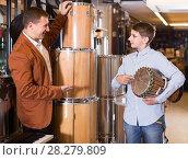 Купить «Father and teenage son examining drum units in guitar shop», фото № 28279809, снято 29 марта 2017 г. (c) Яков Филимонов / Фотобанк Лори