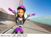 Купить «African girl in helmet rollerblading at skate park», фото № 28280521, снято 14 октября 2017 г. (c) Сергей Новиков / Фотобанк Лори