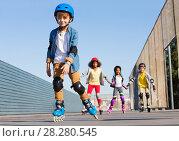 Купить «Schoolboy in helmet rollerblading with his friends», фото № 28280545, снято 14 октября 2017 г. (c) Сергей Новиков / Фотобанк Лори