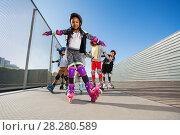 Купить «African girl rollerblading with hands like wings», фото № 28280589, снято 14 октября 2017 г. (c) Сергей Новиков / Фотобанк Лори