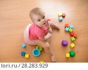 Купить «baby sits on a children's pot, toilet, playing with toys», фото № 28283929, снято 8 ноября 2019 г. (c) Оксана Кузьмина / Фотобанк Лори