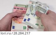 Купить «Пересчет купюр в руках, евро и доллары», видеоролик № 28284217, снято 26 февраля 2018 г. (c) Кекяляйнен Андрей / Фотобанк Лори