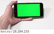 Человек водит по кругу руку с телефоном с зеленым экраном. Стоковое видео, видеограф Кекяляйнен Андрей / Фотобанк Лори