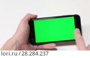 Человек перелистывает пальцем закладки на телефоне, зеленый экран. Стоковое видео, видеограф Кекяляйнен Андрей / Фотобанк Лори