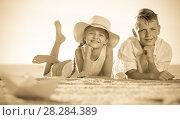 Купить «boy and girl lying on sandy beach», фото № 28284389, снято 19 июня 2019 г. (c) Яков Филимонов / Фотобанк Лори