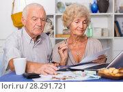 Купить «Serious retired couple calculating bills», фото № 28291721, снято 28 августа 2017 г. (c) Яков Филимонов / Фотобанк Лори