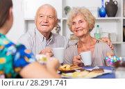 Купить «Smiling elderly spouses enjoying tea with girl», фото № 28291741, снято 28 августа 2017 г. (c) Яков Филимонов / Фотобанк Лори