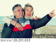 Купить «Mature couple walks outdoors and point by hand», фото № 28291833, снято 18 августа 2018 г. (c) Яков Филимонов / Фотобанк Лори