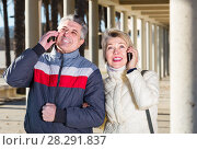 Купить «smiling husband and wife go nearby with each other and speak by mobile phone», фото № 28291837, снято 20 августа 2019 г. (c) Яков Филимонов / Фотобанк Лори