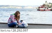 Купить «The girl is doing homework on the quay near the sea», видеоролик № 28292097, снято 17 октября 2017 г. (c) Tatiana Kravchenko / Фотобанк Лори
