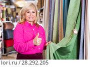 Купить «seller showing curtain and holding thumb up», фото № 28292205, снято 17 января 2018 г. (c) Яков Филимонов / Фотобанк Лори