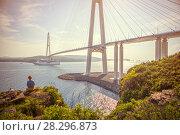 Купить «Девушка сидит на скале, смотрит на Русский мост и проходящий под ним пассажирский лайнер», фото № 28296873, снято 30 мая 2017 г. (c) Ева Монт / Фотобанк Лори