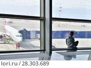 Купить «Moscow, Russia - April 4. 2018. child through window looks at plane in airport Vnukovo», фото № 28303689, снято 4 апреля 2018 г. (c) Володина Ольга / Фотобанк Лори